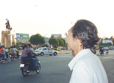Nhà thơ Trần Tuấn Kiệt với Tượng Trần Nguyên Hãn trước chợ Sài Gòn. (Hình: Viên Linh)