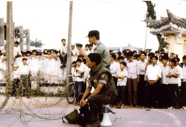 Tại khu vực Đại học Văn Khoa Huế, 1971, Thiếu Tá Liên Thành (ngồi) đang cùng lực lượng cảnh sát sẵn sàng trấn áp một cuộc bạo loạn của sinh viên nằm vùng Đại học Huế trong mục đích chống quân sự học đường, chống chiến tranh, chống Việt Nam Cộng Hòa, và yêu cầu Mỹ rút quân của Tổng hội sinh viên Đại học Huế.